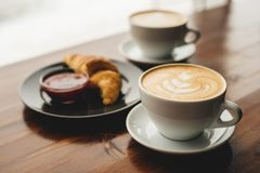 Two cups of cappuccino and croissant royalty free stock photo