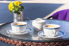 Two cups of cappuccino stand on glass table Stock Photography
