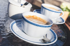 Two cups of cappuccino stand on table in cafe Royalty Free Stock Images