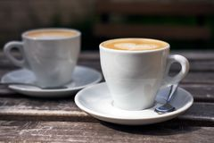 Two cups of cappuccino on the table. Two white cups of cappuccino on the table royalty free stock photos