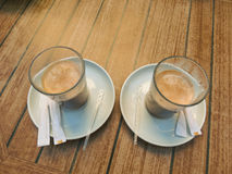 Two cups of cappuccino. On the table are two white saucers glass cup of cappuccino Stock Photo