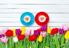 Two cups of Cappuccino and tulips Royalty Free Stock Images