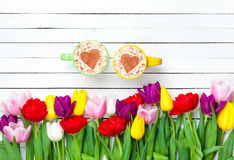 Two cups of Cappuccino and tulips Royalty Free Stock Photography