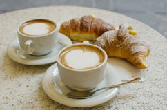 Two cups of cappuccino with two croissants. Stock Images