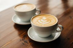 Two cups of cappuccino on the wooden table. royalty free stock photography