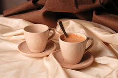 Two cups of cappuchino. On coffee with milk coloured cloth background Royalty Free Stock Photo