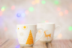 Two cups and christmas lights on background. Two cups with gold ornate and christmas multi color lights on background Stock Image