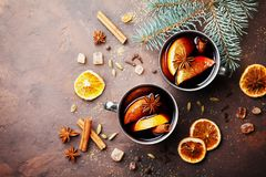 Two cups of christmas mulled wine or gluhwein with spices and orange slices on rustic table top view. Traditional drink on winter Royalty Free Stock Photography