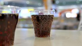 Two cups of coca cola on table. Inside shopping mall stock video