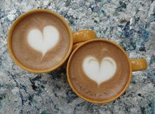 Two coffe cups. Two cups of coffe with hearts decorations. outdoors table. park food Royalty Free Stock Image