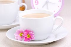 Two Cups Of Coffee. Cups filled with coffee in with clock in the background Stock Photo