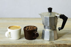 Two cups of coffee and beans and percolator. On wood Stock Images