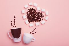 Two cups  with coffee beans in  the shape of  heart royalty free stock photos