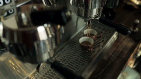 Two cups of coffee being poured from a espresso stock video footage