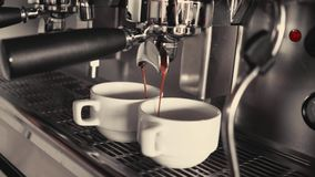 Two cups of coffee being poured from a professional espresso machine. Close-Up. Concept of coffee making, service. Catering stock video footage
