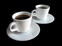 Two cups of coffee on black. Two white cups of coffee isolated on black background Stock Images