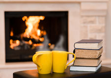 Two cups of coffee with books on the background of the fireplace