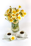 Two cups of coffee and a bouquet of camomiles Stock Images