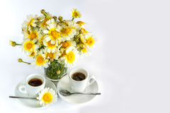 Two cups of coffee and a bouquet of camomiles on a white background Royalty Free Stock Photography