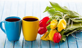 Two cups of coffee and bouquet of tulips Royalty Free Stock Images