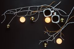 Two cups of coffee, branches, candles and Christmas toys on a dark background. stock photography
