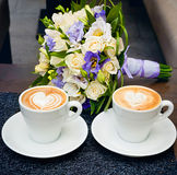 Two cups of coffee, with bridal bouquet. Royalty Free Stock Photography