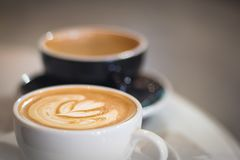 Two cups of coffee in cafe, white one with heart shape latte art, black one with beautiful bokeh as background Royalty Free Stock Image
