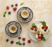Two cups of coffee and cakes with raspberries and blueberries. On a marble background - top view Stock Photo