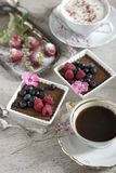 Two cups of coffee, chocolate desserts and strawberries, vintage cutlery stock image
