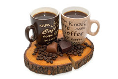 Two cups of coffee, chocolate hearts and coffee beans on the stump Royalty Free Stock Image