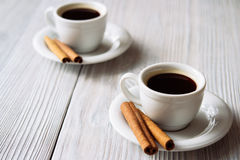 Two cups of coffee with cinnamon sticks on a white wooden table Royalty Free Stock Image