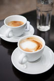 Two cups of coffee. Closeup of two milk based coffees in white cups on cafe table with glass of water in background Royalty Free Stock Photography