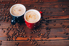 Two cups of coffee with coffee beans. Two polka dots coffee cups with foam lying on  wooden table with coffee beans Royalty Free Stock Photos