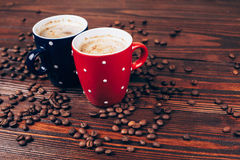 Two cups of coffee with coffee beans. Two polka dots coffee cups with foam lying on  wooden table with coffee beans Stock Image