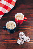Two cups of coffee with cookies. Two polka dots cups of coffee with foam and cookies standing on wooden table with italian checkered tablecloth Stock Photos