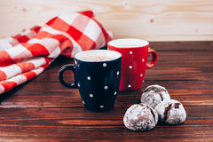 Two cups of coffee with cookies. Two polka dots cups of coffee with foam and cookies standing on wooden table with italian checkered tablecloth Royalty Free Stock Image