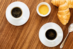 Two cups of coffee with croissants. Two cups of coffee with croissants, honey and sachets sugar on wooden table. top view Stock Images