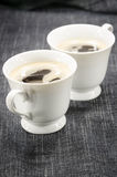 Two cups of coffee on denim background Stock Images