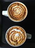 Two cups of coffee with design in froth. Two white cups of coffee on black background with pattern in foam on top Stock Photos