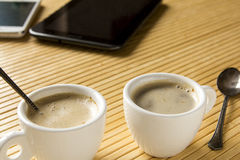 Two cups of coffee on the desk next to the tablet computer and m. Two cups of coffee with foam on the desk next to the tablet computer and mobile phone Royalty Free Stock Photos