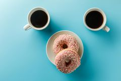 Two cups of coffee and donuts. Copy space. Top view royalty free stock photo
