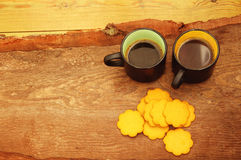 Two cups of coffee and figured cookies. Two black cups of coffee and figured yellow ginger cookies on the made old wooden background Royalty Free Stock Images