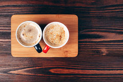 Two cups of coffee with foam. Standing on wooden board, on wooden table Royalty Free Stock Image