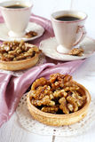 Two cups of coffee and a French dessert, Walnut caramel tart Royalty Free Stock Images