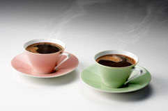 Two cups of coffee on a gray background. Two cups of black coffee on a gray background Stock Photography