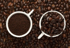 Two cups of coffee. Two cups of ground coffee and roasted coffee royalty free stock image