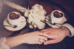 Two cups of coffee and hand of bride and groom Royalty Free Stock Photos