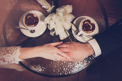 Two cups of coffee and hand of bride and groom Royalty Free Stock Images