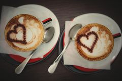 Two cups of coffee with heart pattern. In a white cups on wooden background. Love concept Stock Images