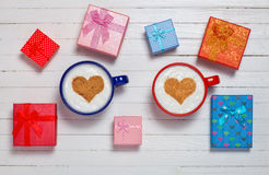 Two cups of coffee with heart shape symbol and gift boxes Stock Photo